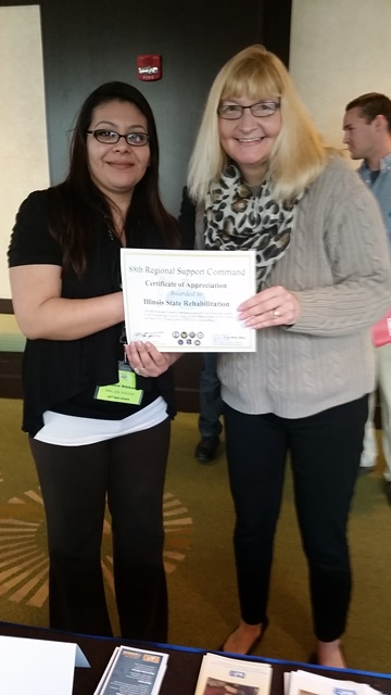 Lisa A. Ruggio, Yellow Ribbon Reintegration Program, U.S. Army Reserve (left) presents a certificate to Rehabilitation Case Coordinator Maria Raedeke (right).